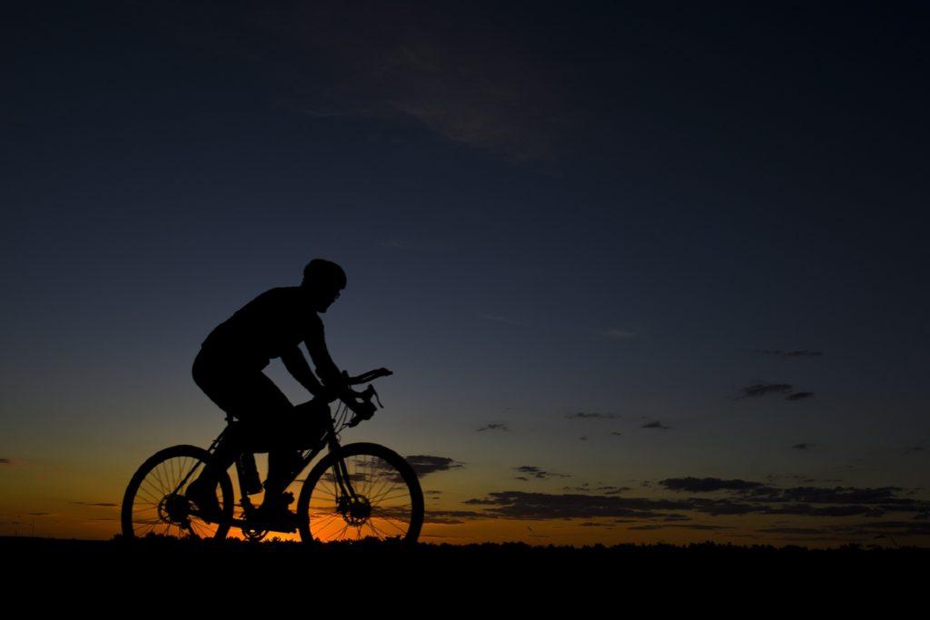 a man biking against the sunset