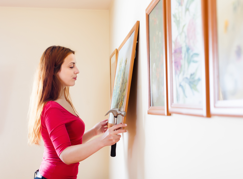 a woman hanging art in her apartment