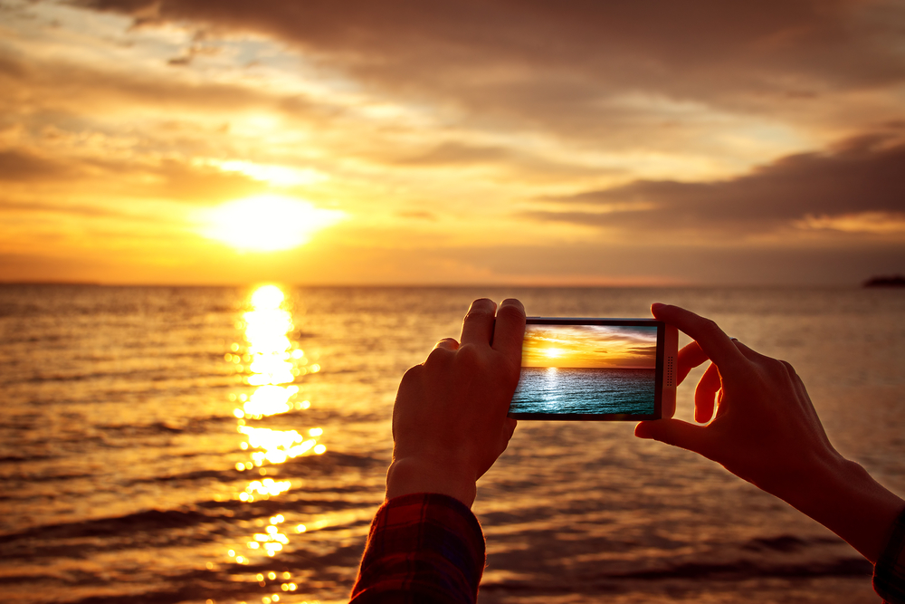 taking a photo of a sunset