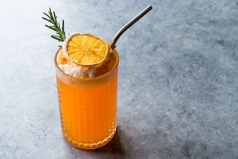 a stainless steel straw in an orange cocktail