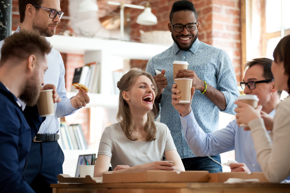 employees laughing and drinking coffee at work