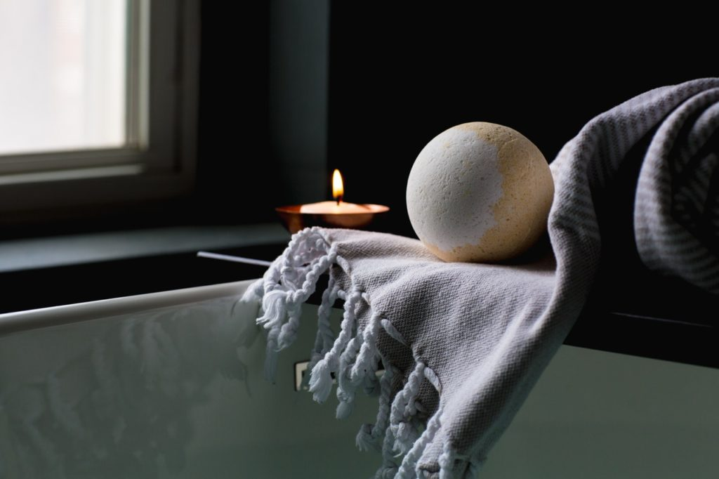 a bath bomb, towel, and a candle by the bathtub