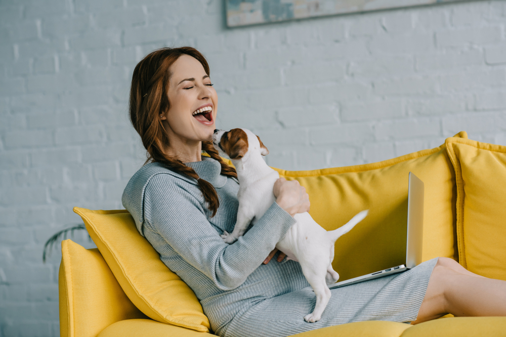 laughing on the couch with a dog