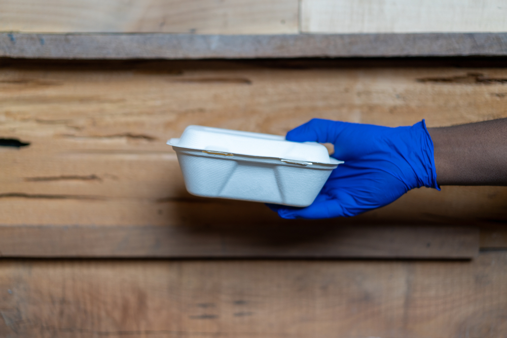 a takeout box with a glove