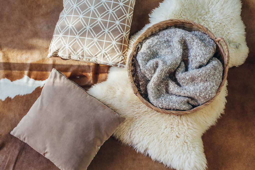 a cozy blanket in a basket with throw pillows