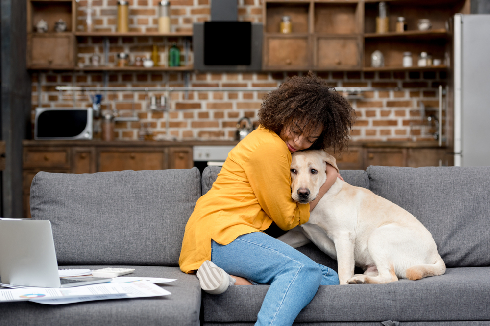 hugging a dog in an apartment | pet-friendly home decor tips