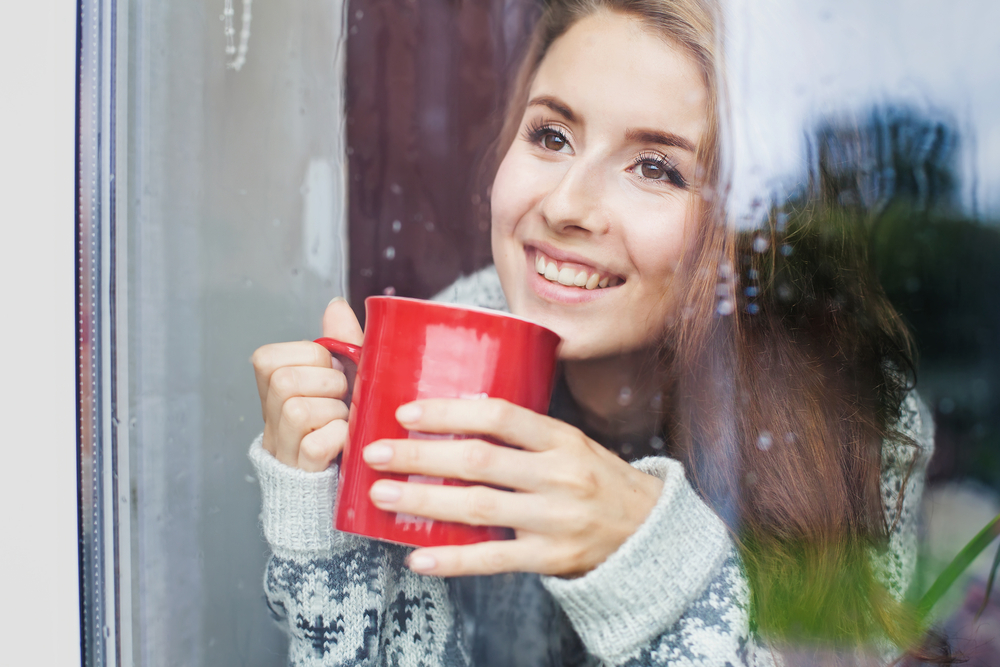 smiling and looking out window at rain with a mug   rainy day activities