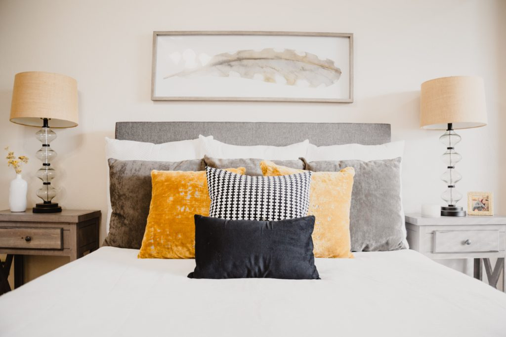 colorful pillows on a bed | summer decor for the bedroom